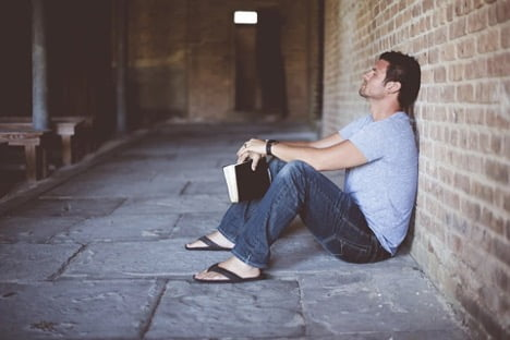 Law of attraction man sitting leaning against the wall with book in hand