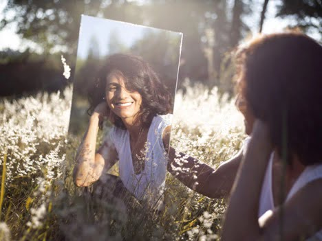 self love affirmations beautiful women smiling staring into a mirror in a open field