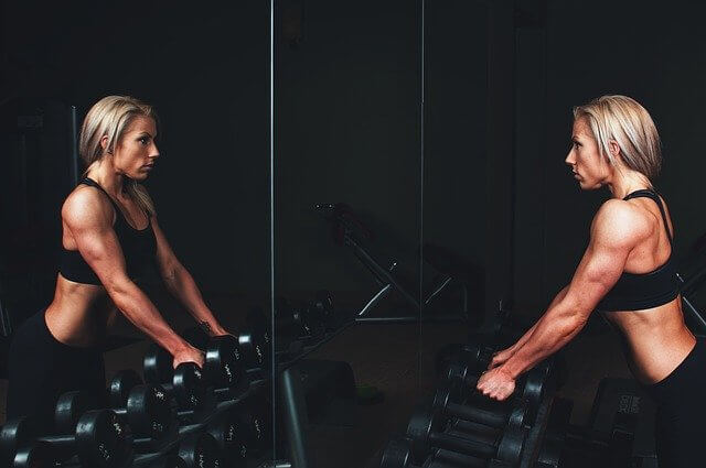 beautiful blond women in the gym staring in the mirror concept of Self-love techniques
