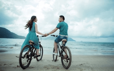 Couple riding a bike by the sea shore