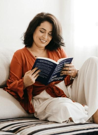 Dark Haired woman reading a book while sitting on the bed