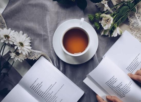 Reading a book while drinking tea