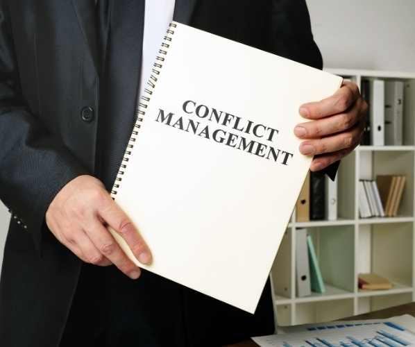 man holding a notebook marked Conflict Management
