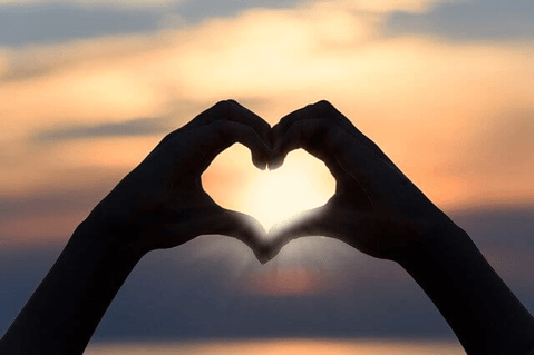 hands make a heart-shaped silhouette at sunset