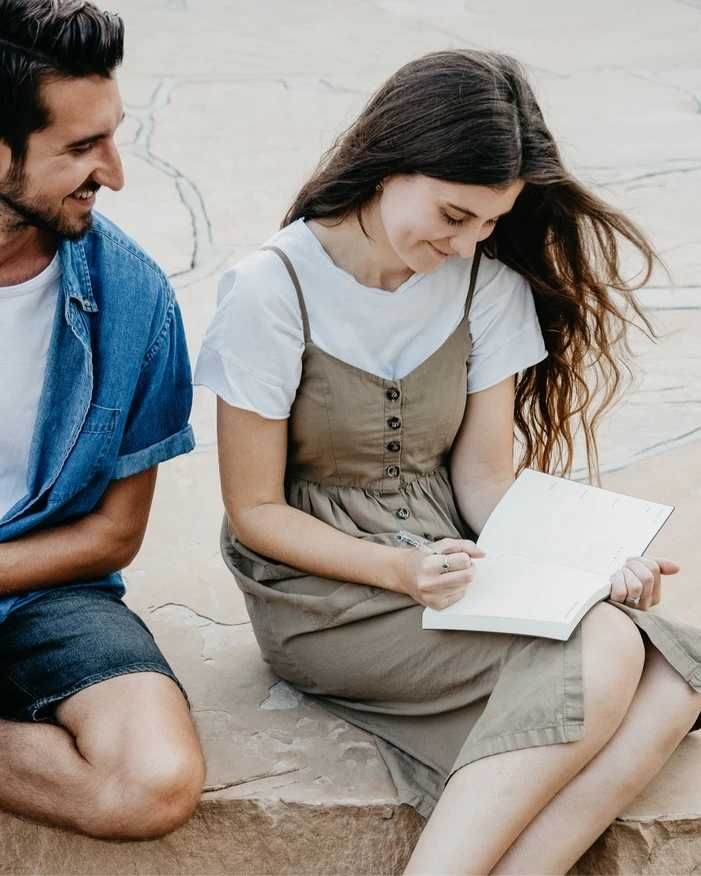 Man smiling to a woman who is writing on a planner