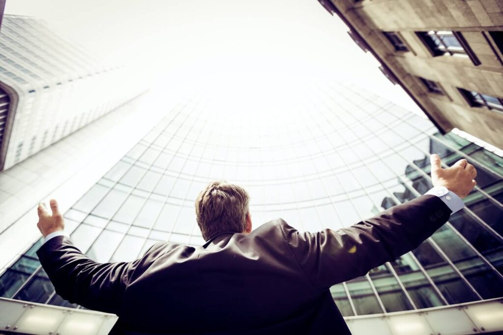 Man in a suit raising his hands in the air - How to deal with failure