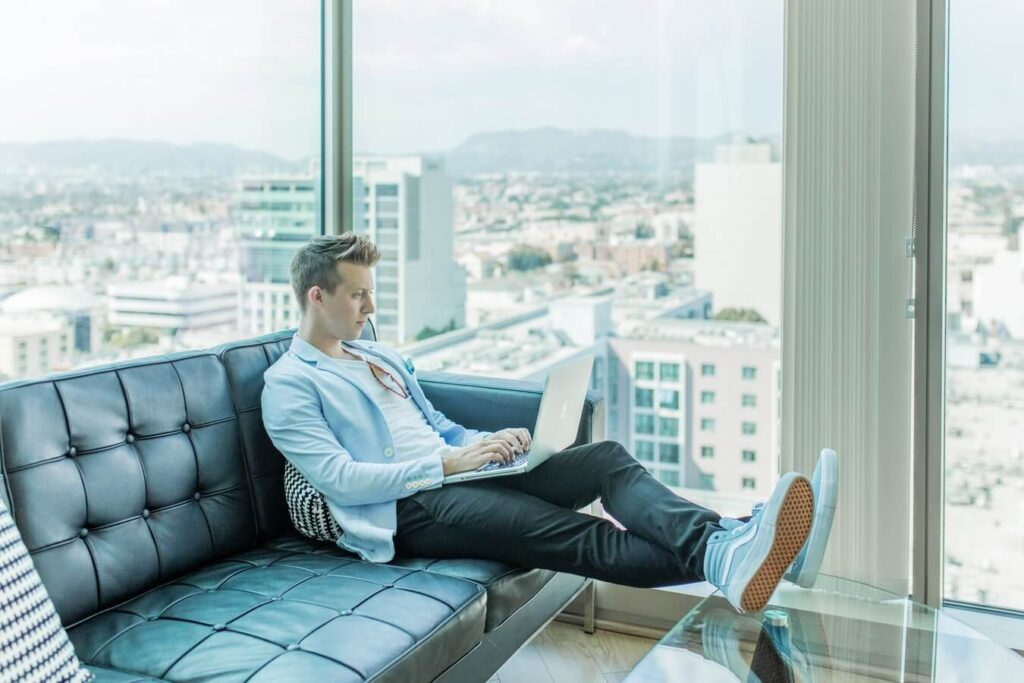 Man sitting on the sofa while using laptop - Personal and professional development