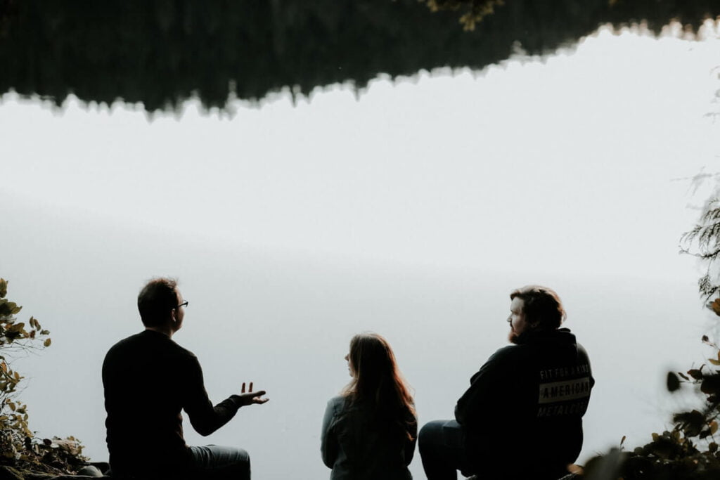 A group of people talking beside a lake - how confidence affects communication