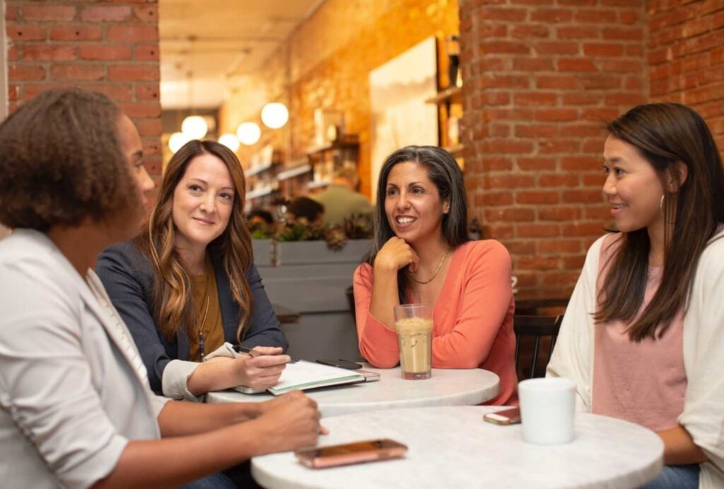 Group of people talking while sitting around dinner table - interpersonal and group communication