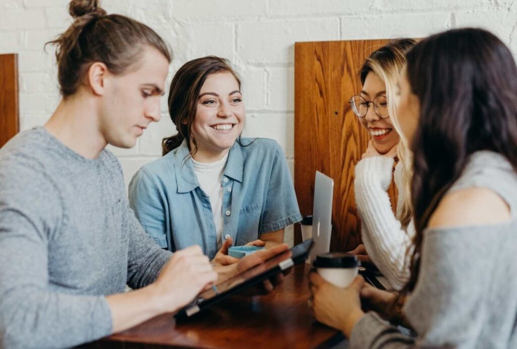 Group of people talking to each other over coffee