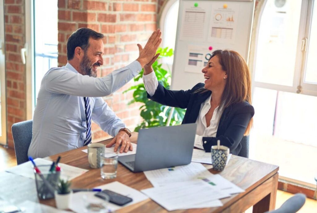 Coworkers high fiving - interpersonal and group communication