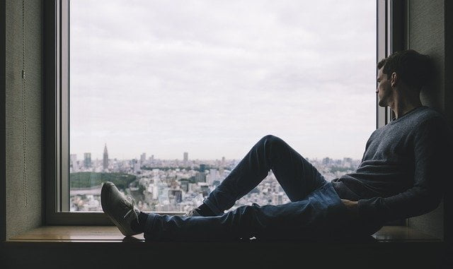 Man laying down and looking outside the window