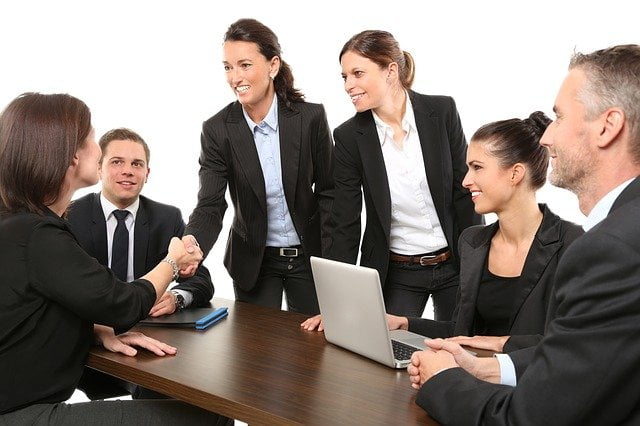 A Group of people in suits gathered around a table - Can a shy person run a business and be successful?